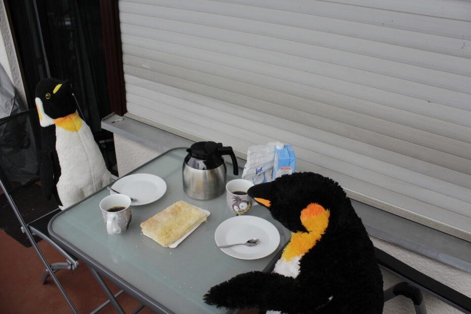 zwei Pinguine bei Kaffee und Kuchen