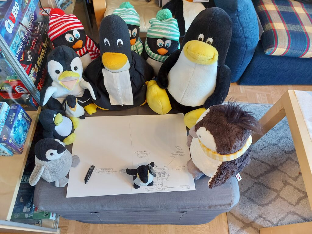 Pinguine sitzen um den Plan herum und beraten den abschließenden Entwurf